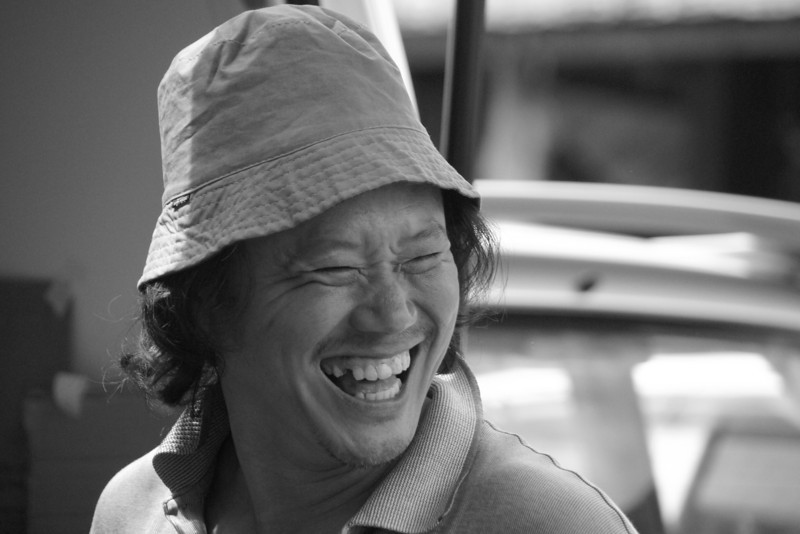 A man in Malaysia flashes a wide grin as he laughs hysterically at a joke told by somebody else in front of him in Penang, Malaysia.