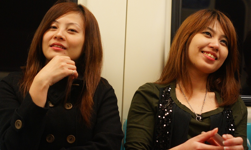 Today's smiling faces travel photo is of a couple of Taiwanese ladies smiling while taking the Metro (MRT) around downtown Taipei - Formosa, Taiwan.