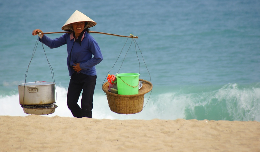 Today's smiling faces travel photo is of a Vietnamese local vendor carrying a yoke with fishing supplies at a beach in Nha Trang, Vietnam.