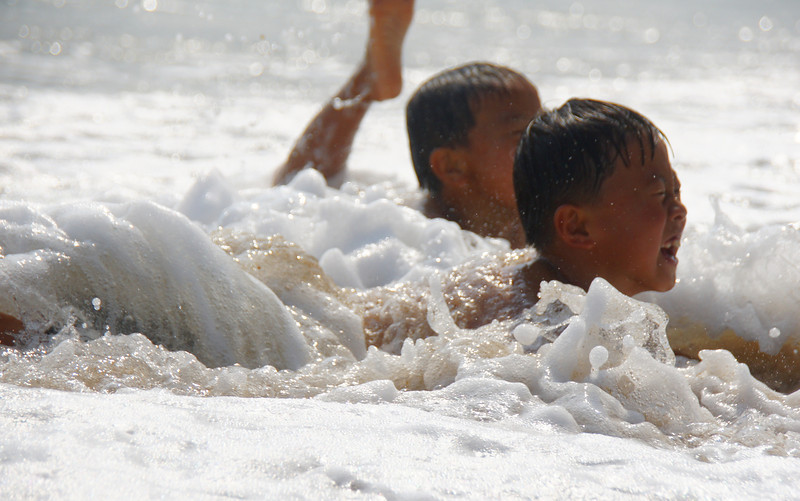 Today's smiling faces travel photo is an action shot of 2 Vietnamese boys splashing and playing together at the beach in Nha Trang, Vietnam.