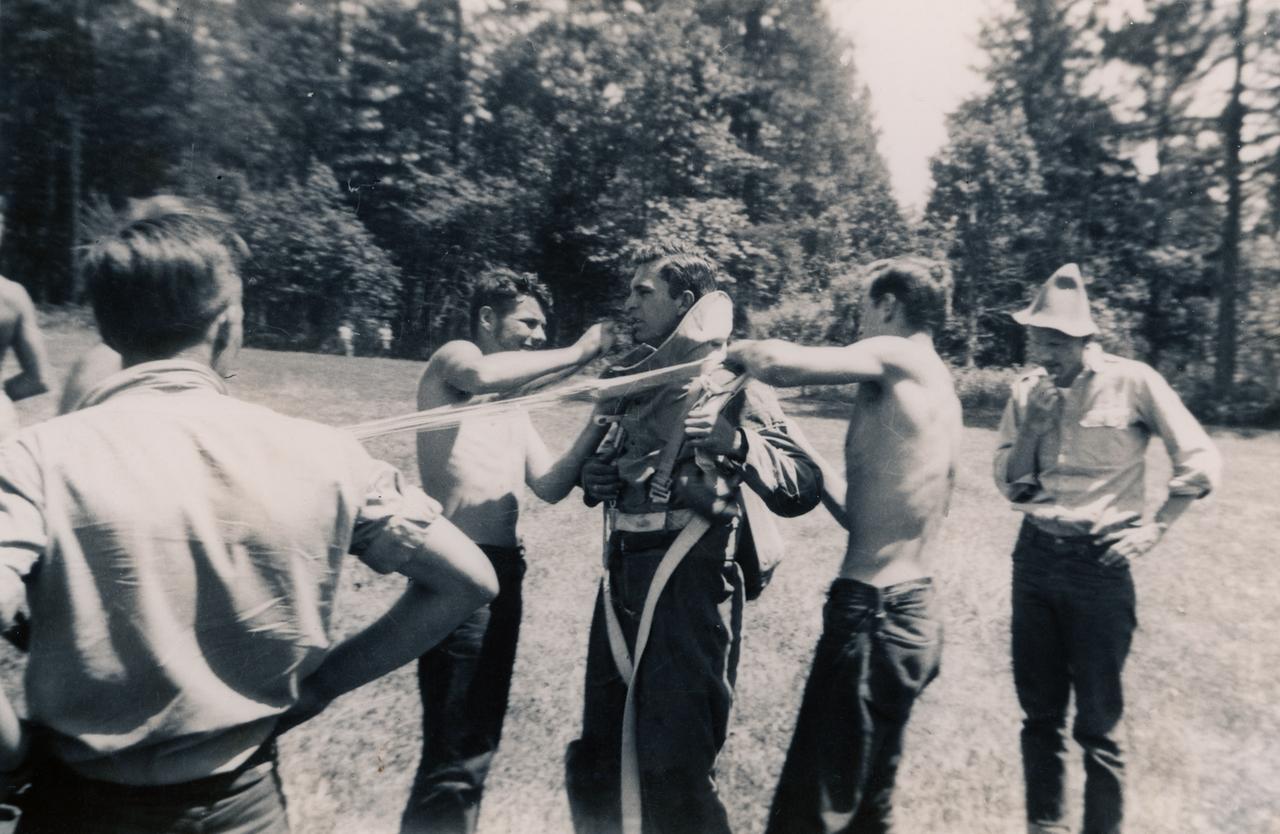 Bob Nolan (CJ-47) in jump suit, Bob Snyder (CJ-48) with back to photo, Starr Jenkins (CJ-48) (cap)<br /> Contributor: Albert Boucher