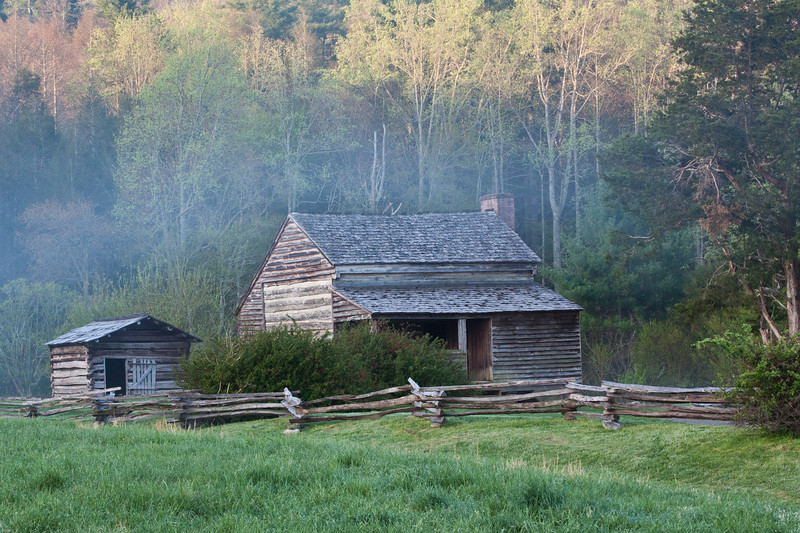 The Lawson Cabin with the sun coming up over the hills and the mist starting to dissipate.