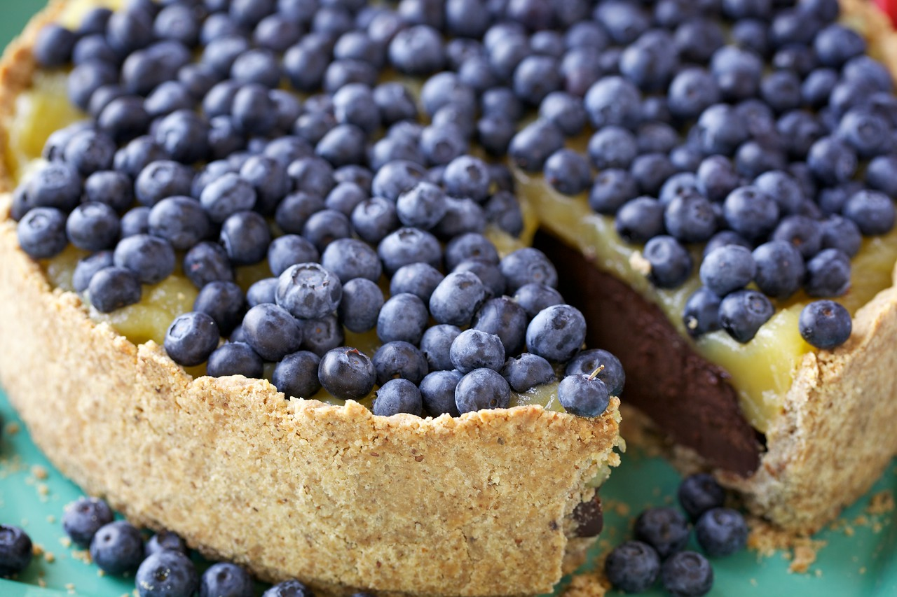 Walnut crust with dense chocolate filling, fresh lemon curd and blueberries