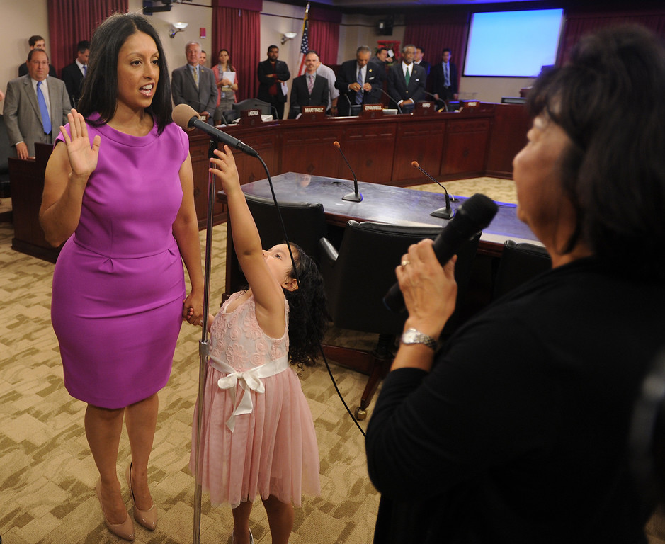 . Nury Martinez is sworn into office by City Clerk June Lagmay while her daughter Isabella Guzman plays with the microphone stand. Martinez is the newest Los Angeles City Councilwoman and is representing District 6. The council met in Van Nuys City Hall. Van Nuys , CA. 8/2/2013(John McCoy/LA Daily News)