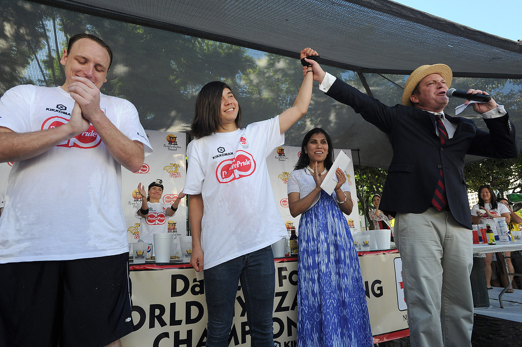 . (l-r) Joey Chestnut reacts to his loss as Matt Stonie has his hand raised in victory by Sam Barclay. Malaysia Airlines Israt Akhter waits to award a round trip to Tokyo to the winner. The World Gyoza Eating Contest is taking place as part of the annual Nisei Week Foundation festival. Matt Stonie of San Jose ended up setting a new world record by eating 268 pot stickers, edging out last years winner Joey Chestnut who ate 251. Los Angeles, CA. 8/17/2013(John McCoy/LA Daily News)