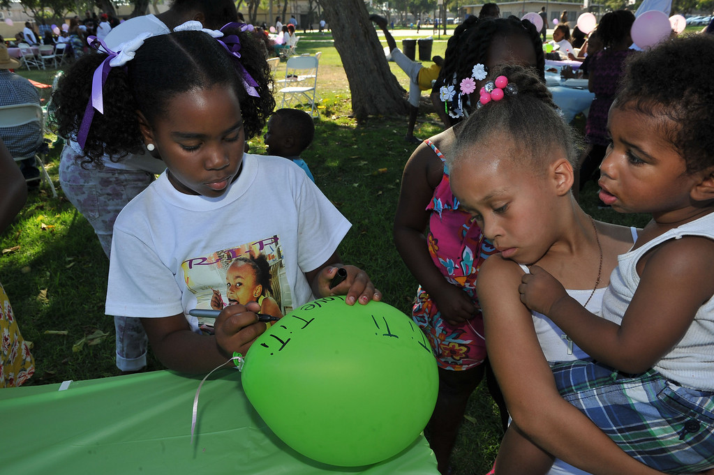 . 9/14/13 - Damanee Moore writes a message of love to her cousin on a balloon. After a morning funeral family and friends of Tiani Ricks gathered Saturday afternoon at Simms Park in Bellflower for her originally planned birthday party. Ricks was killed at a party in Moreno Valley a week before she would have turned 7 years old. She lived and attended school in Long Beach. (Photo by Brittany Murray/Press Telgeram)