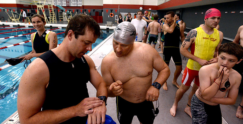 Bob Raines--Montgomery Media<br /> Shawn Gallgher, left, and Chris McDemus check their timers as they wait to line up in the high school pool for the swimming portion of the Upper Dublin Triathlon Sunday, May 17, 2015.