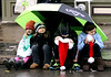 While Connor Wilson, 5, checks how much candy he has accumulated in his Santa hat, Sophie and Olivia Krey, 5 and 8, and Kate Wilson wait on the curb under a big umbrella waiting for Santa and Mrs. Claus to put in an appearance at the Ambler Holiday Parade Saturday, Dec. 6, 2014.<br /> Bob Raines-Montgomery Media