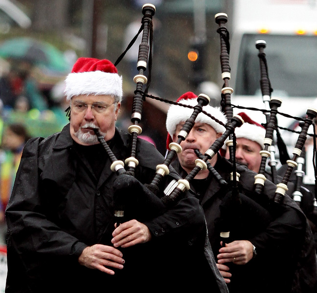 Pipers from Irish Thunder Pipes and Drums wear Santa hats and raincoats during the annual Ambler Holiday Parade on a rainy Saturday morning, Dec. 6, 2014.<br /> Bob Raines-Montgomery Media