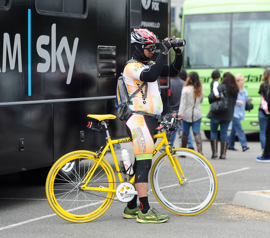 . A spectator takes photos of teams as they arrive at the start of Stage 7 of the Amgen Tour of California in Ontario, Ca. on Saturday, May 16, 2015. (Staff Photo by Sarah Alvarado/ Inland Valley Daily Bulletin)
