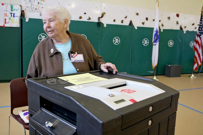 Charlotte Cramm mans the ballot box at the polls at John R. Briggs Elementary School gym on Tuesday morning. SENTINEL & ENTERPRISE/ JOHN LOVE