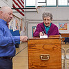 Ashby residents came to the town's elementary school on Monday to vote in the annual town election. On left is Bob Raymond, who manned the ballot box during the election; Grace Swanson, on right, casts her vote. SENTINEL & ENTERPRISE/ ASHLEY LUCENTE