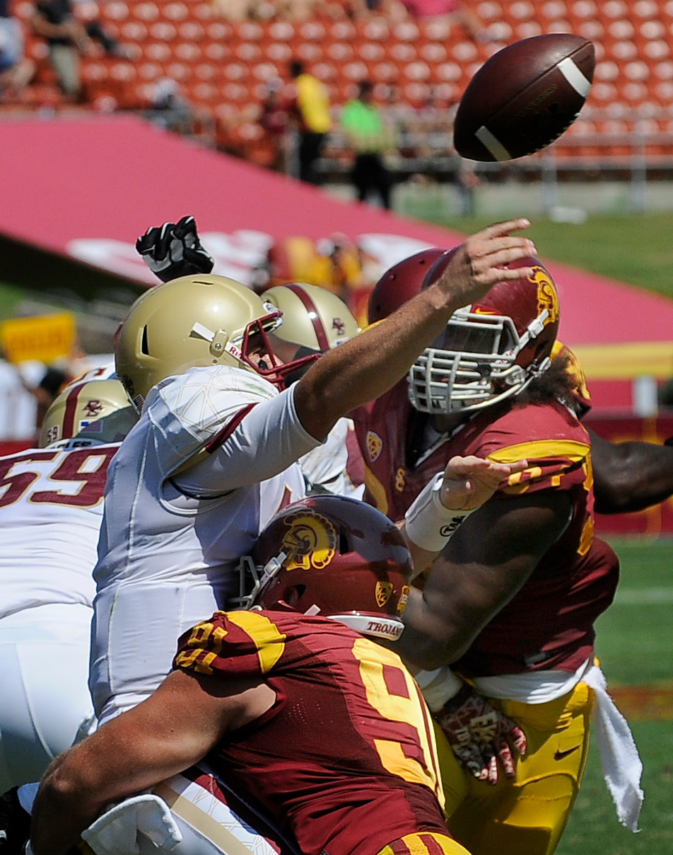 Description of . Boston College QB Chase Rettig gets the pass away under heavy pressure from #91 Morgan Breslin and #94 Leonard Williams in the 3rd quarter.  USC defeated Boston College 35-7 in a game played at the Coliseum in Los Angeles, CA. 9/14/2013. photo by (John McCoy/Los Angeles Daily News)