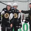 From left, Burlington native, hockey defenseman Brien Diffley (74), Mark Hamilton, and Max Iafrate, listen to skating instructor Kim Brandvola at Boston Bruins development camp.  (SUN/Julia Malakie)