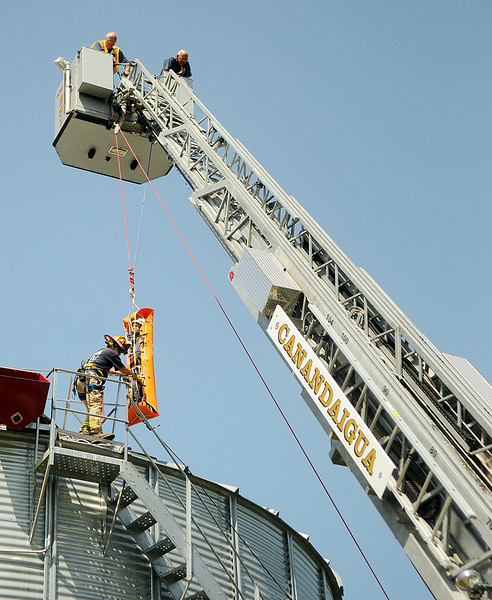 Jack Haley/Messenger Post Media<br /> The Platform ladder truck was used as an anchor point and members of the the Ontario County Rope Team hauled up a voluteer portraying a victim from inside the huge grain bin.