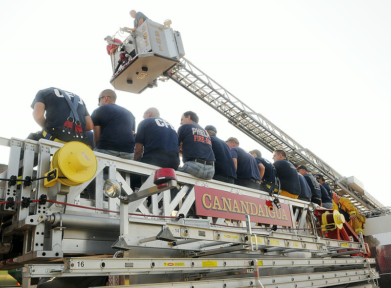 Jack Haley/Messenger Post Media<br /> Firefighters watch a demonstration on how fast a wagan containing an auger can grasp a person and drag it down through the machinery.
