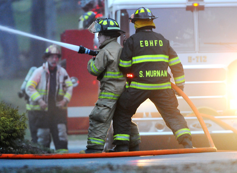 Jack Haley/Messenger Post Media<br /> East Bloomfield firefighters make an outside attack while interior firefighters get their SCBA equipment on at a house in the village on Main Street Monday evening.