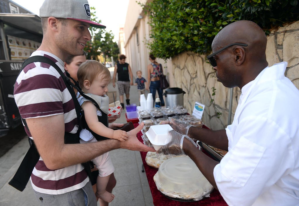 . San Pedro resident Jordan Wanner and his Daughter Eve Wanner, 10 Months, get some treats from Gerald Thompson\'s Sucker For Cake,  at  First Thursday Artwalk,  Visit downtown San Pedro�s art galleries, restaurants and shops and enjoy entertainment. Pedro, Thursday, July 6, 2017.            ( Photo by Stephen Carr /  Daily Breeze / SCNG )