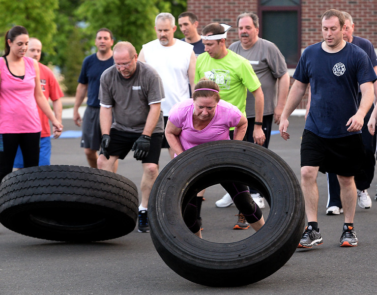 "Bob Raines--Montgomery Media<br /> Fort Washington firefighters race to flip truck tires end-over-end over the length of the back apron of the firehouse during one of their ""boot camp"" physical training sessions."