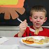 Jordan Roberts, 8, of Ashburnham enjoys some turkey during Goodrich Academy's holiday dinner held at the school on Tuesday night.  SENTINEL & ENTERPRISE/JOHN LOVE