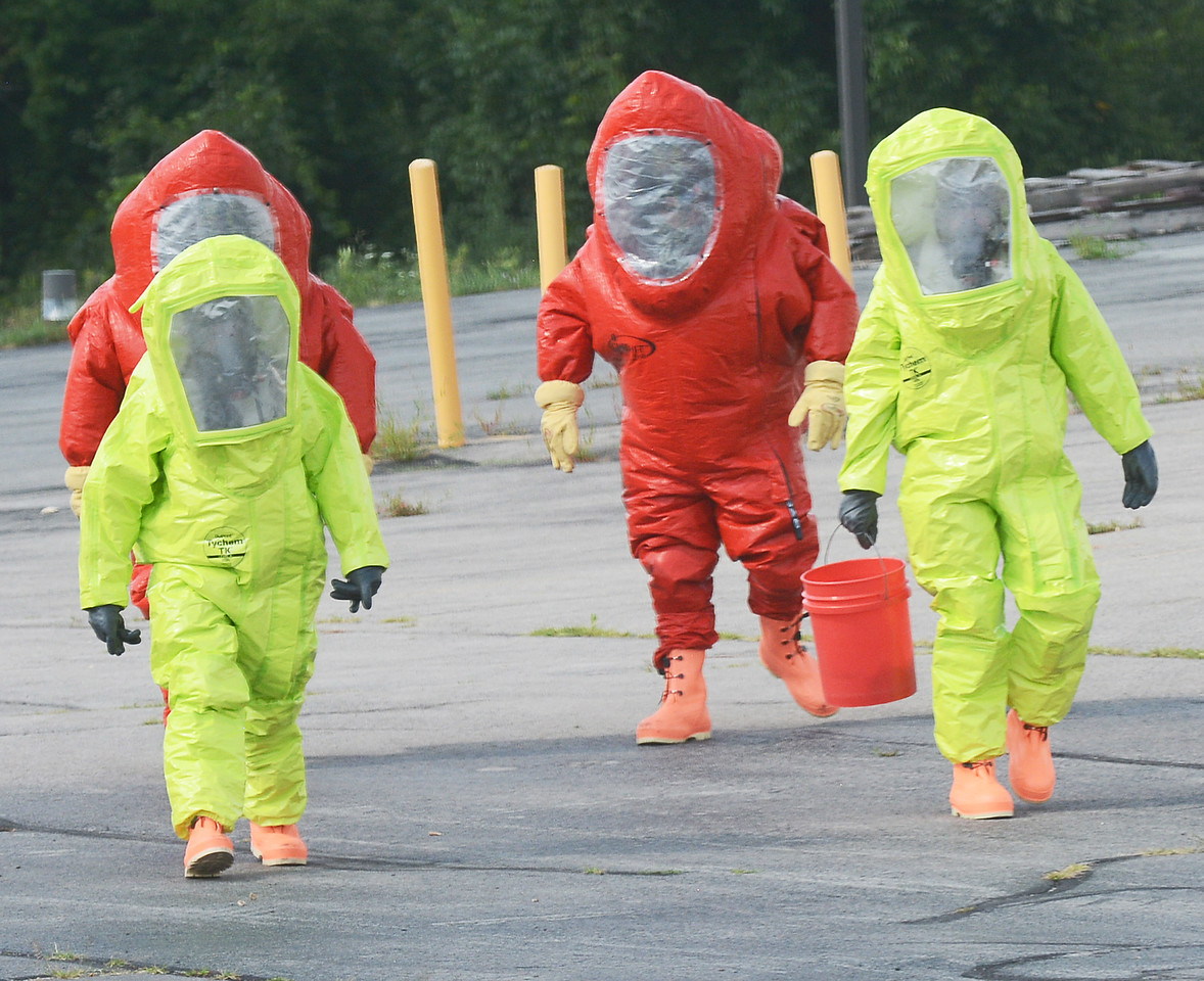 Jack Haley/Messenger Post Media<br /> Local firefighters in area Haz Mat units exit the building after checking on the condition of the spill.