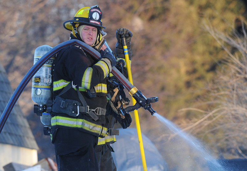 (Jack Haley/Messenger Post Media)<br /> A Seneca Castle firefighter keeps the nozzle cracked to keep from freezing as several departments assited Hopewell on a structure fire early Tuesday evening on County Road 47 near Route 488.