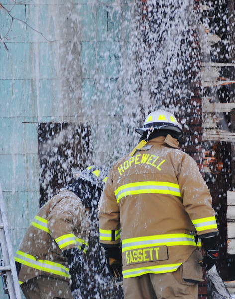 (Jack Haley/Messenger Post Media)<br /> Water being used to hit hotspots inside the structure fall onto some Hopewell firefighters working on the outside of the house.