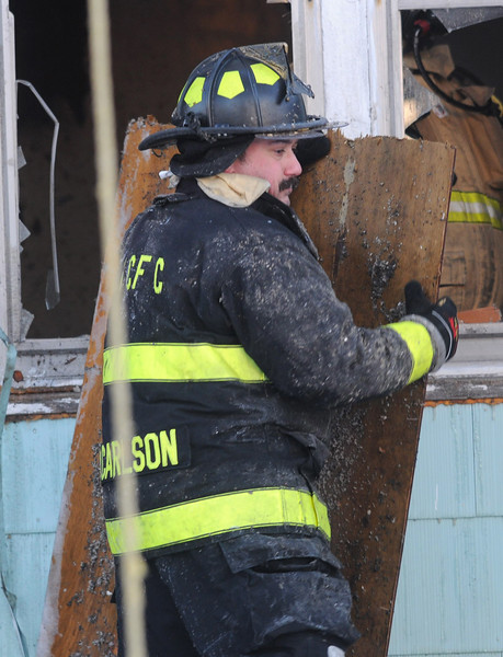 (Jack Haley/Messenger Post Media)<br /> A Seneca Castle firefighter takes some plywood handed out a window and moved out of the way.