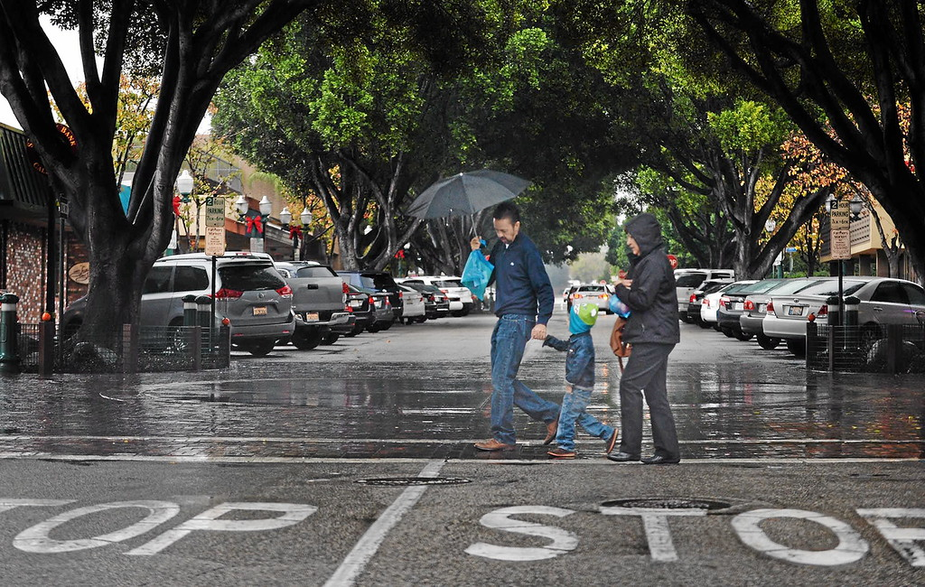. A trio walks across State Street in the rain on Tuesday, Dec. 30, 2014, in Redlands. (Photo by Micah Escamilla/Redlands Daily Facts)