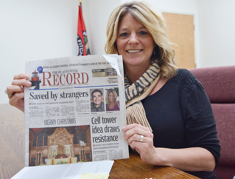 Karen Membrino, Principal Clerk of the Fitchburg Board of Health, recently donated bone marrow to a recipient, Frank Palumbo. Membrino shows off a newspaper article written in the St. Augustine Record by Palumbo. SENTINEL & ENTERPRISE / Ashley Green