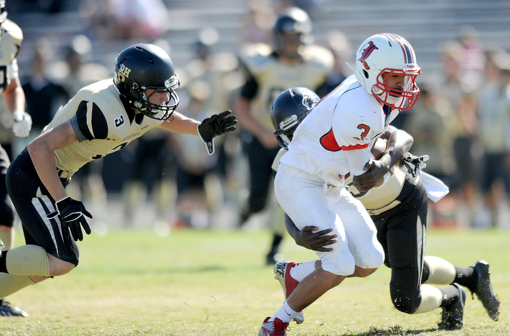 . Peninsula\'s Steven Smith (3), left, and Tobi Ibraheem (5) are unable to bring down Lawndale\'s Anthony Ramirez (3) before reaching the end zone for a touchdown in Friday afternoon\'s high school football game in Rolling Hills Estates in CA. on September 27, 2013. (Photo by Sean Hiller/Daily Breeze)