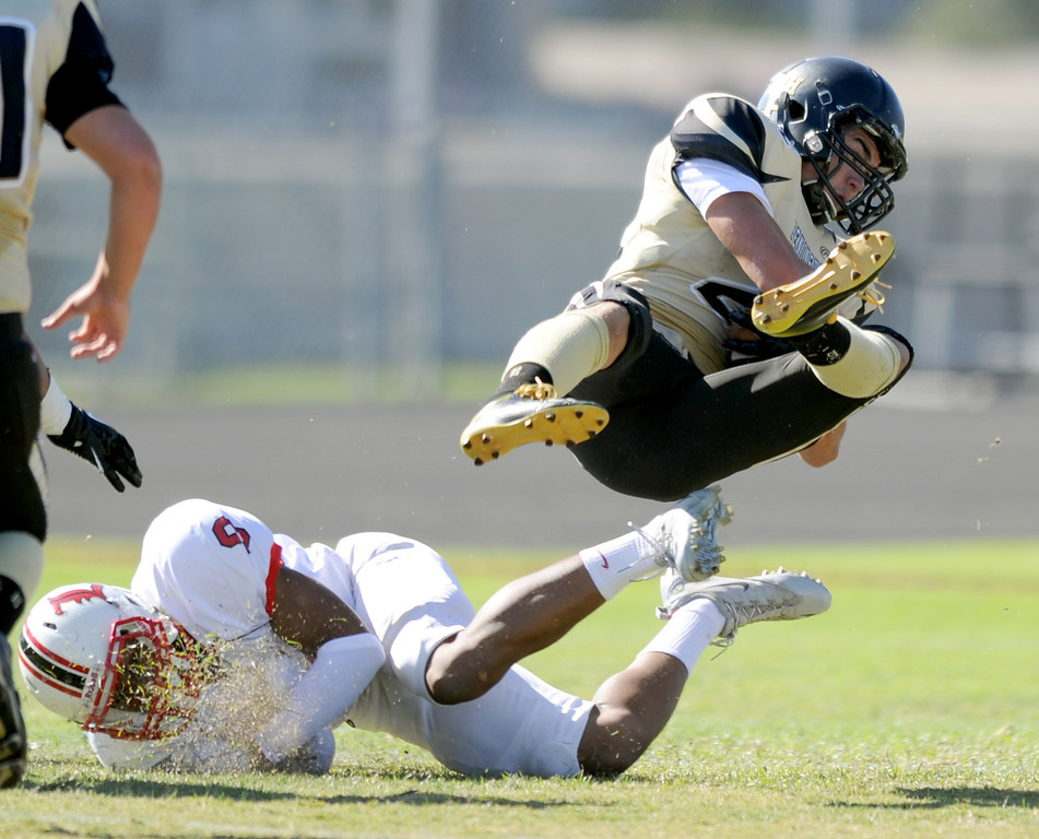 . Peninsula\'s Rory Hubbard (22) sails through the air after being hit by Lawndale\'s Austin Manigo(9) in Friday afternoon\'s high school football game in Rolling Hills Estates in CA. on September 27, 2013. (Photo by Sean Hiller/Daily Breeze)