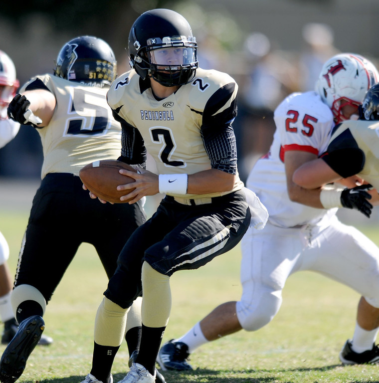 . Peninsula\'s quarterback Ian Escutia looks to pass against Lawndale in Friday afternoon\'s high school football game in Rolling Hills Estates in CA. on September 27, 2013. (Photo by Sean Hiller/Daily Breeze)