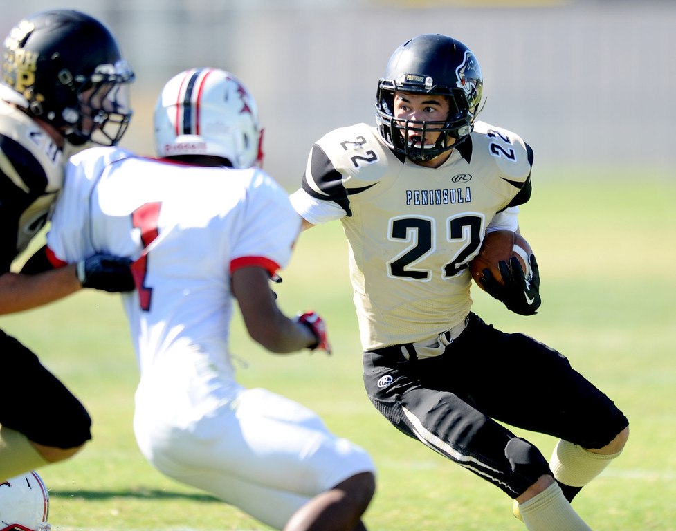 . Peninsula\'s Rory Hubbard (22) on a carry against  Lawndale\'s Engerson Lambert (1)  in Friday afternoon\'s high school football game in Rolling Hills Estates in CA. on September 27, 2013. (Photo by Sean Hiller/Daily Breeze)