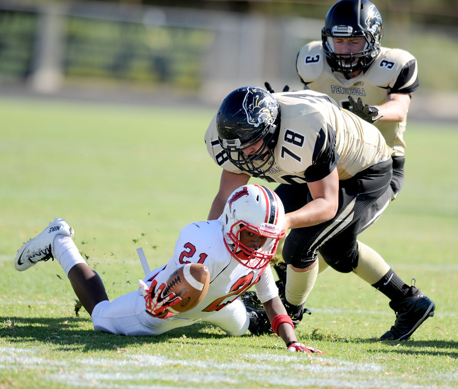 . Lawndale\'s Bryant Perkinson (21) fumbles but recovers the ball ahead of Peninsula\'s Luke Megginson (78) in Friday afternoon\'s high school football game in Rolling Hills Estates in CA. on September 27, 2013. (Photo by Sean Hiller/Daily Breeze)