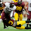 Minnesota Gophers runningback David Cobb breaks a tackle from teammate Derrick Wells, bottom, during the Minnesota Gopher Football scrimmage at TCF Stadium in Minneapolis on August 9, 2014.   (Pioneer Press: Sherri LaRose-Chiglo)
