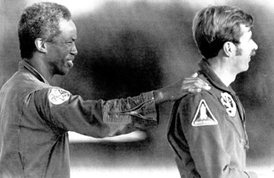 Guion S. Bluford, the nation's first black astronaut, pats the back of crew member Dale A. Gardner on 8/27/83