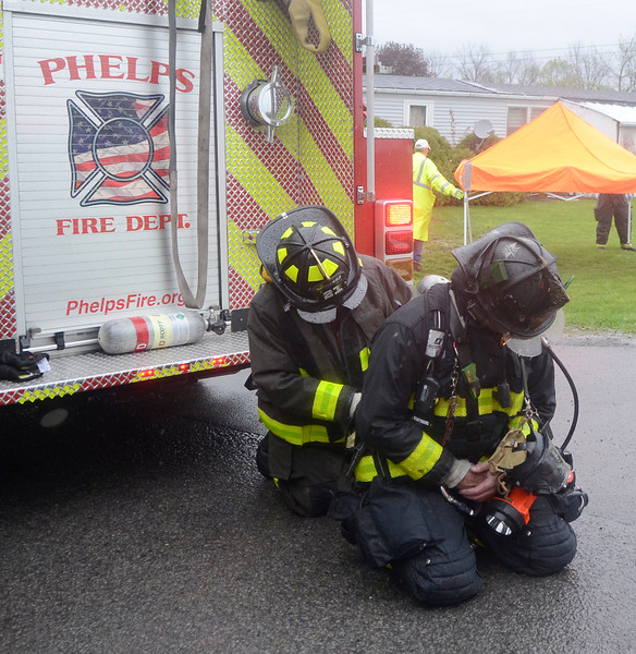 (Jack Haley/Messenger Post Media)<br /> Firefighters from Phelps change their bottles for the Self Contained Breathing Apparatus (SCBA) during Monday's fire.