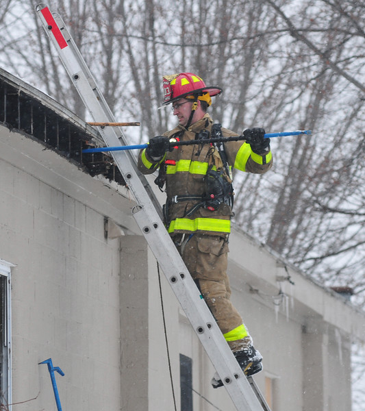 [Jack Haley/Messenger Post Media]<br /> A firefighter from Phelps does overhaul outside of the apartment building on County Road 6, in which Phelps and Oaks Corners were dispatched for the reported structure fire on late Wednesday afternoon.