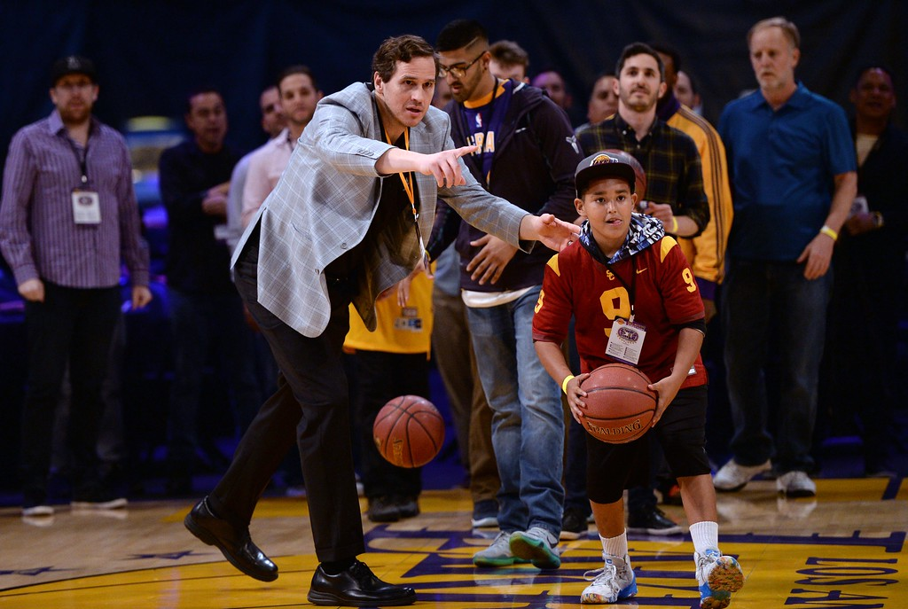 . Former Los Angeles Laker player and now assistant coach for the Lakers Mark Madsen,left, helps fans take a shot at the basket, during The Los Angeles Sports & Entertainment Commission (LASEC) 13th annual LAKERS ALL-ACCESS, at the Staples Center.   Los Angeles  Calif., Monday, February ,27, 2017.            ( Photo by Stephen Carr / Daily News / SCNG )