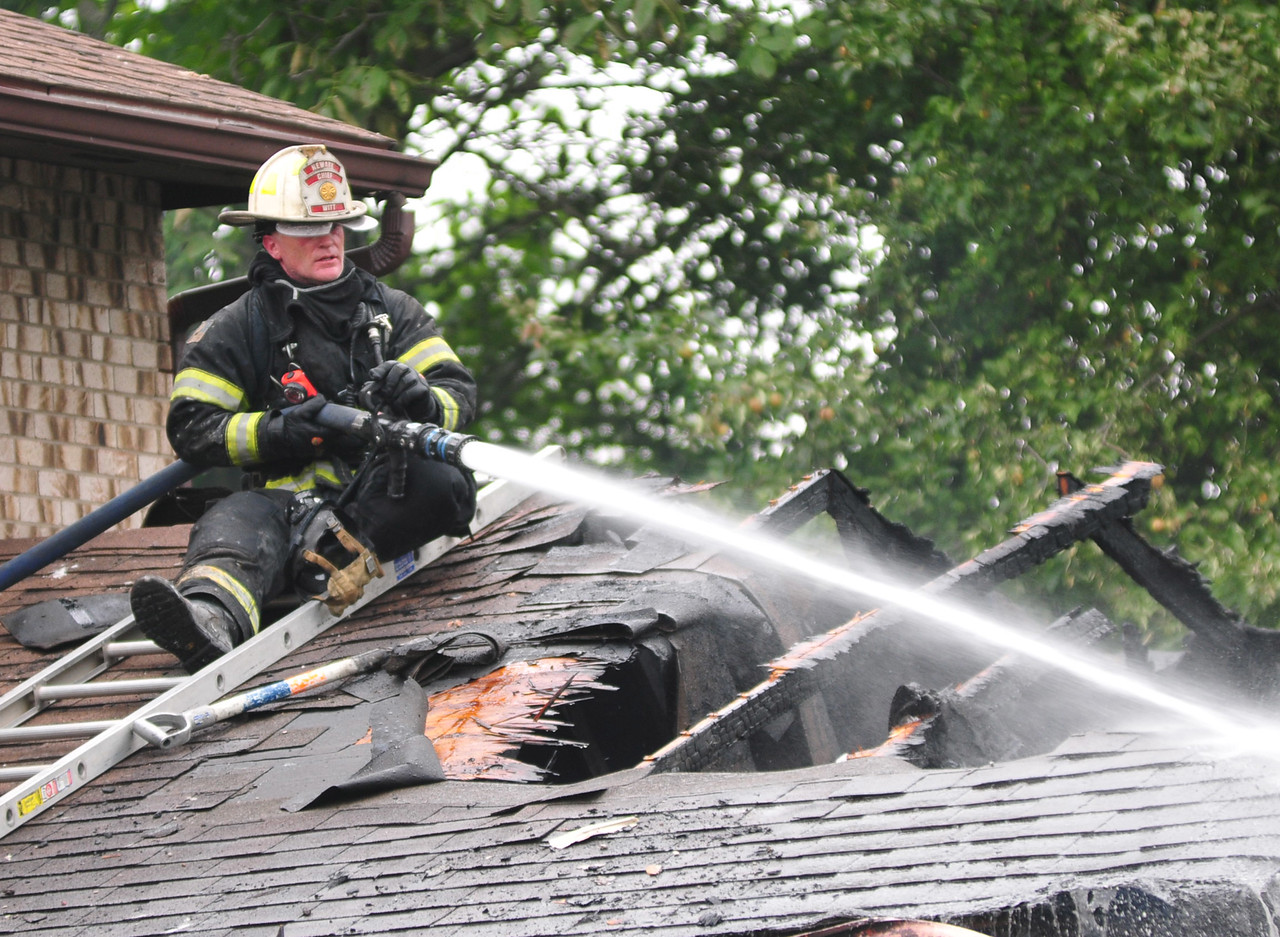 [Jack Haley/Messenger Post Media]<br /> A firefighter from Newark hits some hot spots from up on the roof of a garage that caught on fire on Short Road in Port Gibson on Thursday.
