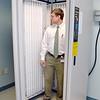 Dermatologist Jeffrey Mailhot, stands inside one of the brand new light treatment machines, a Foldalite III Phototherapy Unit. SENTINEL & ENTERPRISE/ ASHLEY LUCENTE