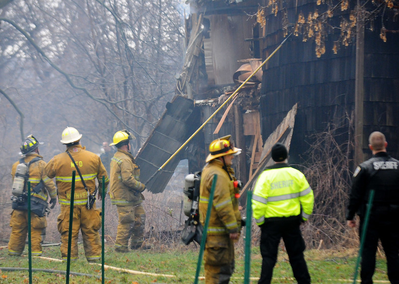 Jack Haley/Messenger Post Media<br /> A firefighter uses a pike pole and pulls down part of the outside wall at the vacant house on the corner of Route 21 and Johnson Road. Firefighters from Shortsville Manchester and Clifton Springs responded to the seen.