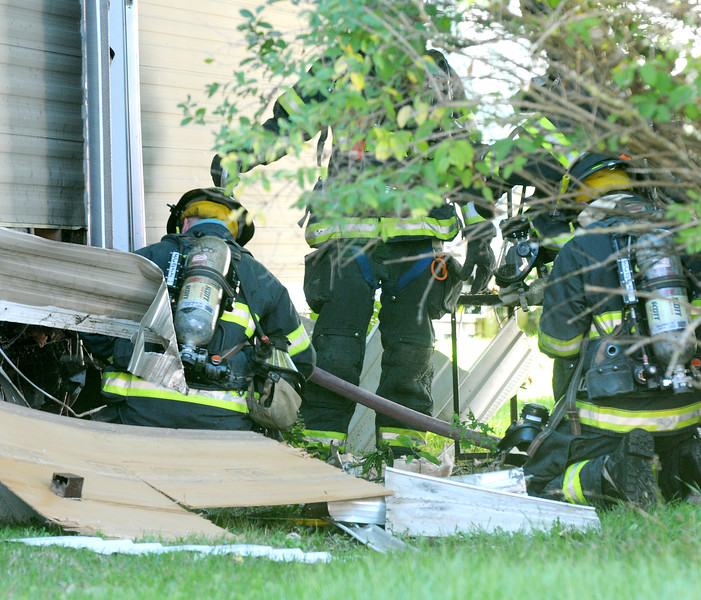 Jack Haley/Messenger Post Media<br /> Canandaigua firefighters begin going underneath the trailer to find the source of  fire Monday afternoon.