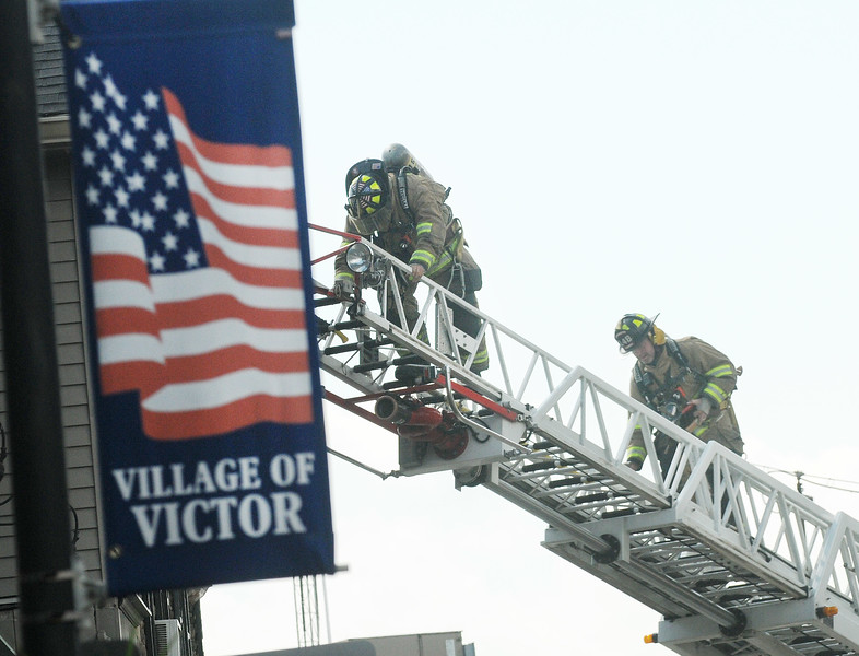Jack Haley/Messenger Post Media<br /> Firefighters climb the ladder to the front of the old Simmonds Store on East Main Street. A fire upstair was quickly extinguished. Numerous fire departments were called to assist, making sure enough firefighters were on hand for the heat as well as equipment.
