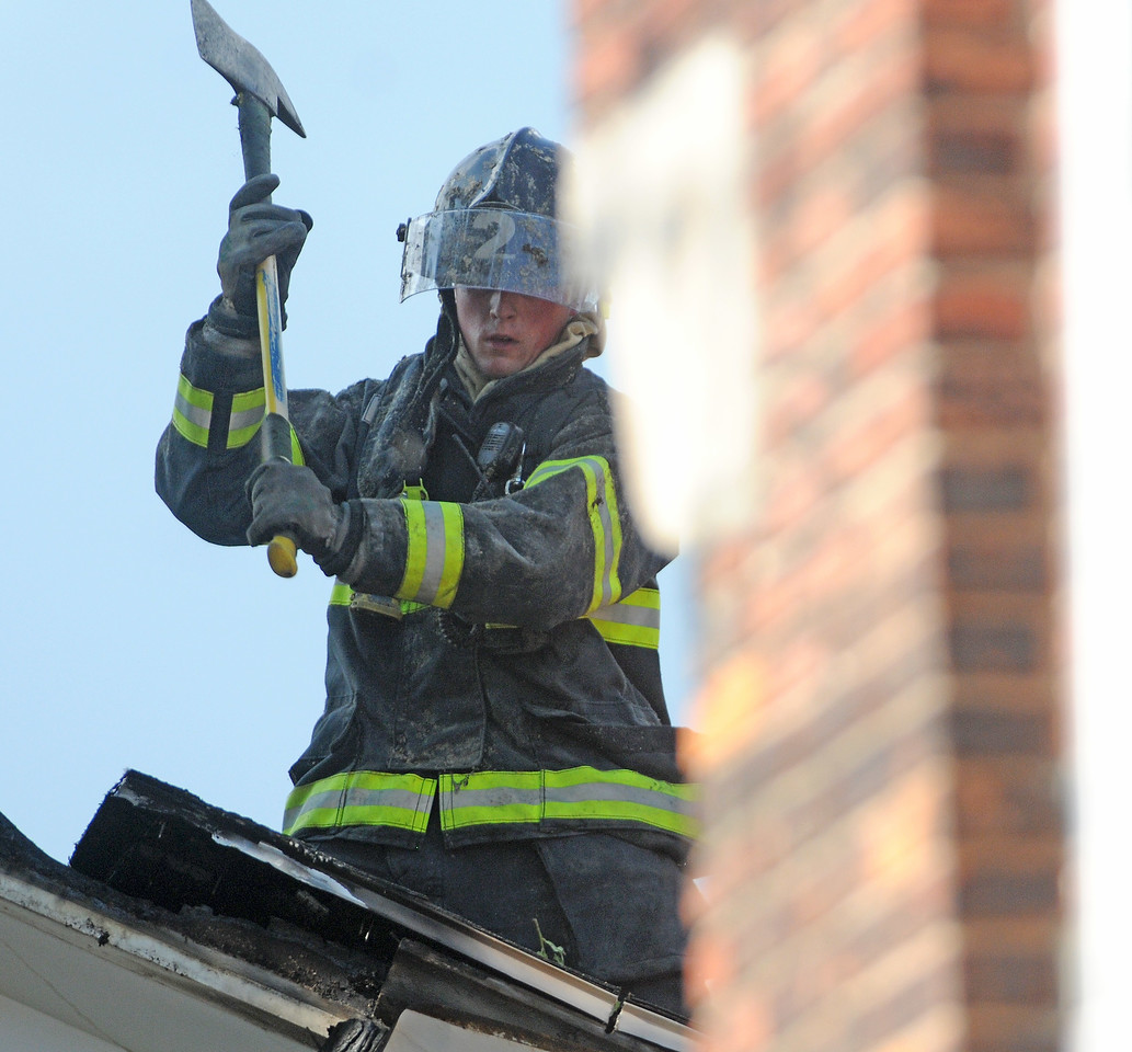 Jack Haley/Messenger Post Media<br /> A firefighter swings an ax on the roof of to gain entry for ventilation and to check for fire extension.
