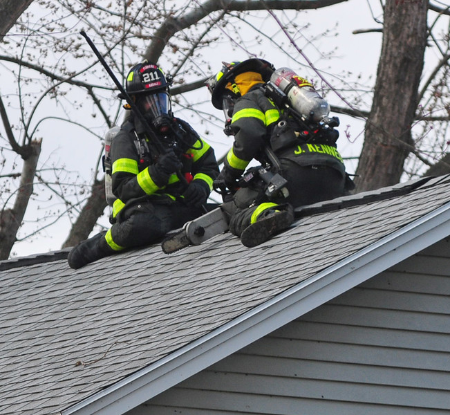 [Jack Haley/Messenger Post Media]<br /> Firefighters from Fishers get ready to ventilate the roof on Brace Road. Victor, Fishers and Farmington  were dispatched to the home and later a second alarm was called bringing in departments from Canandaigua, East Bloomfield, and Egypt to the scene on Wednesday afternoon.