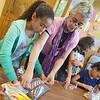 Ashley Echevarri, 10, helps Sally Craigin seal a bag of pet food at the Cleghorn Neighborhood Center on Friday afternoon.  SENTINEL & ENTERPRISE / Ashley Green