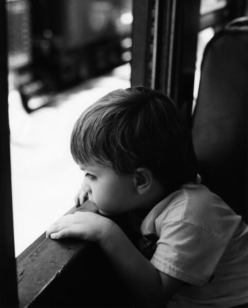 Boy looking through window from train
