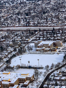 Snow arts; aerial view of city covered with snow in winter. City streets are outlined by snow. Tow municipal building in foreground with a recreation field in between. Perhaps school buildings.